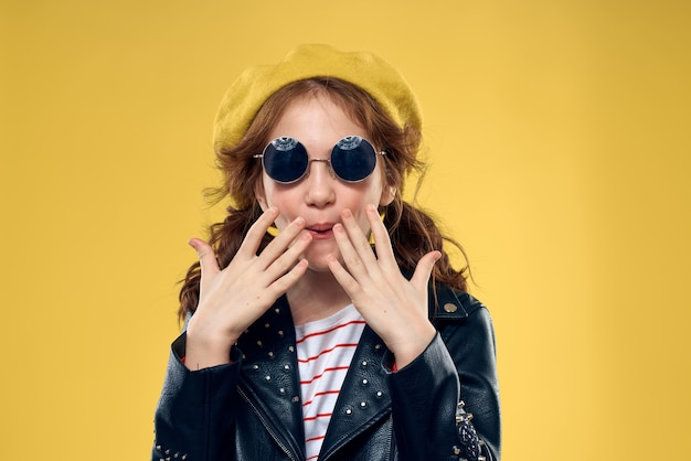 Mała szczęśliwa dziewczyna pozuje w studio, piękne uśmiechnięte dziecko w stylowym wizerunku i skórzaną kurtkę na żółtym tle