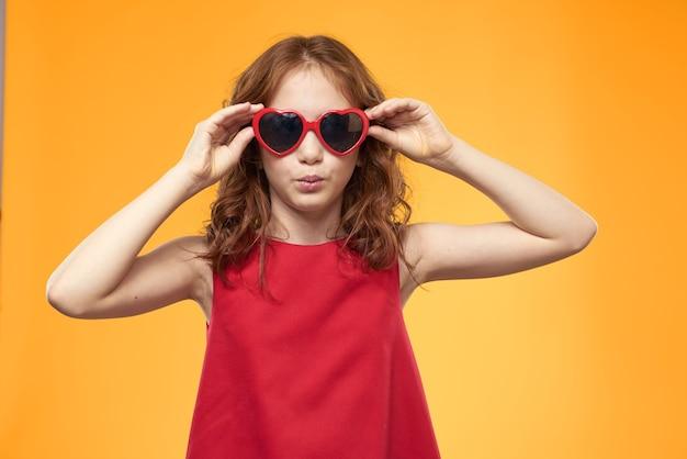 Mała szczęśliwa dziewczyna pozuje z okularami przeciwsłonecznymi