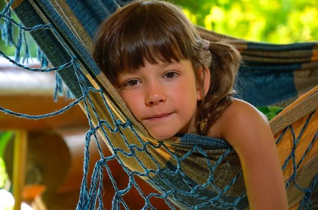 Mała szczęśliwa dziewczyna relaksuje w hamaku. uśmiechnięte dziecko na rodzinne wakacje