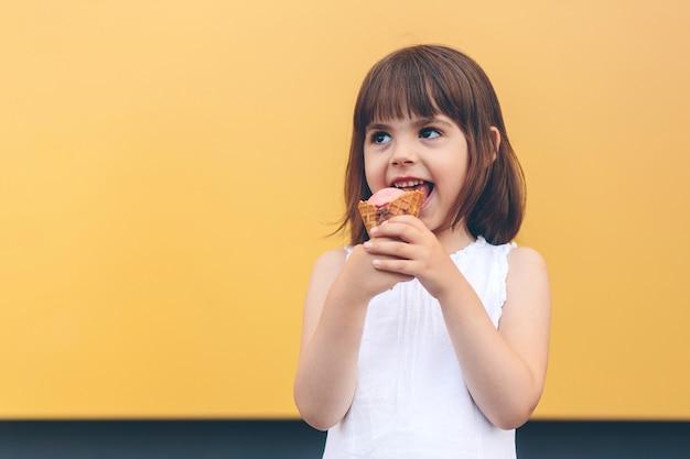 Mała szczęśliwa dziewczynka je lody czekoladowe, na żółtym tle