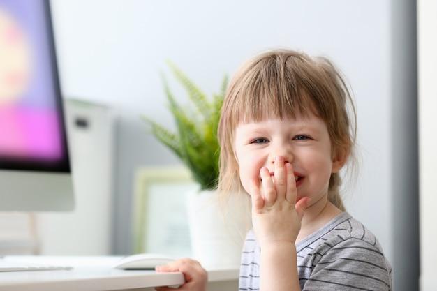 Mała szczęśliwa dziewczynka śmia się zakrywającego usta
