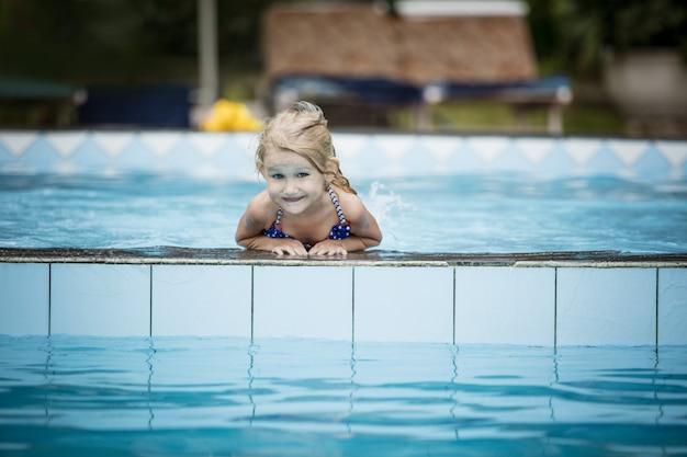 Mała szczęśliwa dziewczynka uśmiecha się i pływa w odkrytym basenie piękna i szczęśliwa