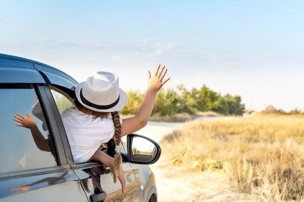 Mała szczęśliwa dziewczynka w kapeluszu podnosi rękę z okna samochodu suv z gnaturem na tlesamochód podróżny