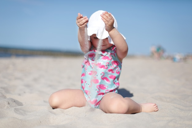 Mała szczęśliwa dziewczynka wylewa biały piasek na plaży, ciesząc się latem, wakacjami
