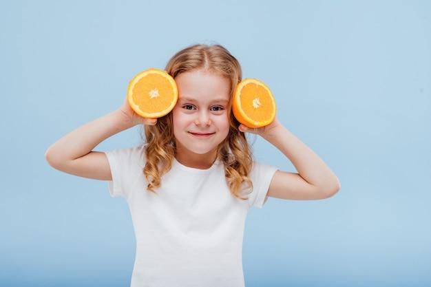 Mała szczęśliwa dziewczynka z pomarańczą w dłoni