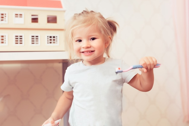 Mała szczęśliwa dziewczynka ze szczoteczką do zębów uśmiecha się i patrzy na kamerę