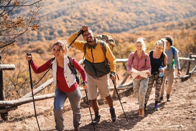Mała szczęśliwa grupa ludzi wycieczkuje jesienią podczas gdy chodzący z rzędu.