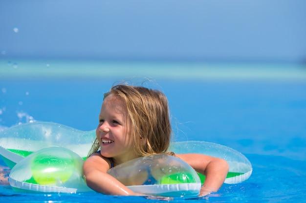 Mała szczęśliwa śliczna dziewczyna w plenerowym pływackim basenie