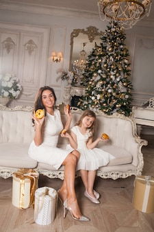 Mała szczęśliwa śliczna dziewczyna z piękną młodą matką, bawiąc się i jedząc pączki na tle udekorowanej choinki w klasycznym wnętrzu. szczęśliwa rodzina w świąteczną noc noworoczną.