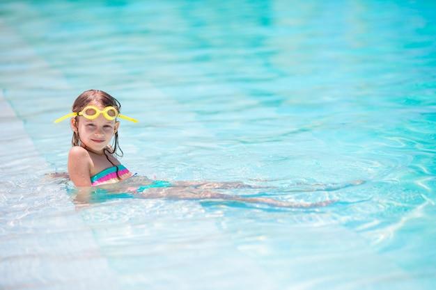 Mała szczęśliwa urocza dziewczyna w plenerowym pływackim basenie