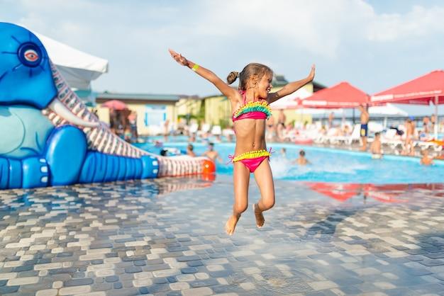Mała szczupła śliczna dziewczyna w jasnym stroju kąpielowym pozuje na tle strefy wodnej dla dzieci na świeżym powietrzu