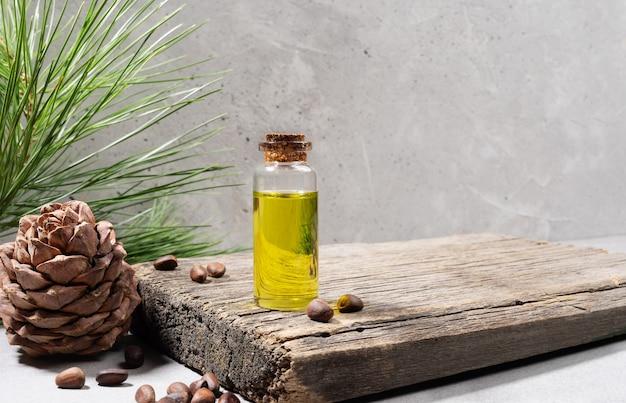 Mała szklana butelka olejku cedrowego na starej desce z gałązką cedrową, stożkiem i orzechami na szaro. ziołolecznictwo i koncepcja iglastych spa. skopiuj miejsce na tekst.