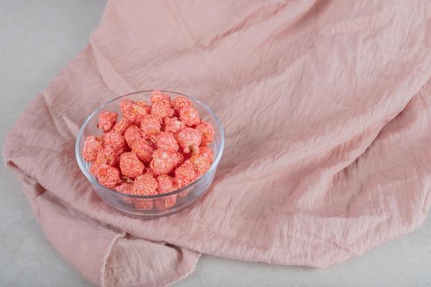 Mała szklana miska z porcją kandyzowanego popcornu na obrusie, na marmurowym stole.