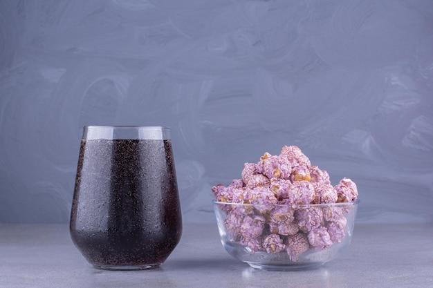 Mała szklanka coli obok małej miski popcornu pokrytego cukierkami na marmurowym tle. zdjęcie wysokiej jakości