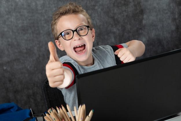 Mała szkolna chłopiec z laptopem pokazuje ok gest