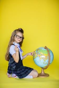 Mała szkolna dziewczyna z kulą ziemską