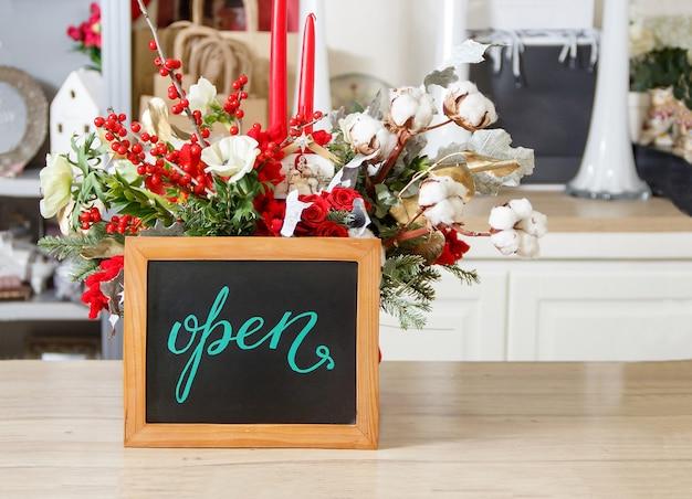 Mała tablica z napisem open w kwiaciarni w okresie świątecznym