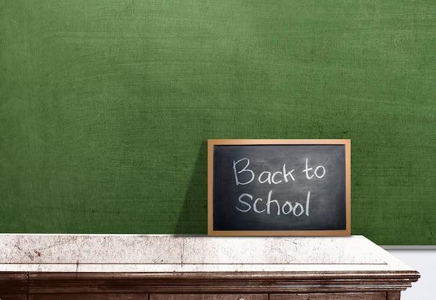 """Mała tablica z napisem """"powrót do szkoły"""" na biurku"""