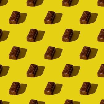 Mała tabliczka czekolady na żółtym tle. wzór. zdjęcie w tle. twardy cień. widok z góry, układ płaski