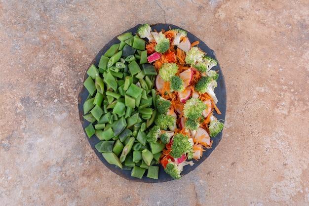 Mała taca z sałatką z mieszanych warzyw i posiekaną fasolą strączkową na marmurowej powierzchni