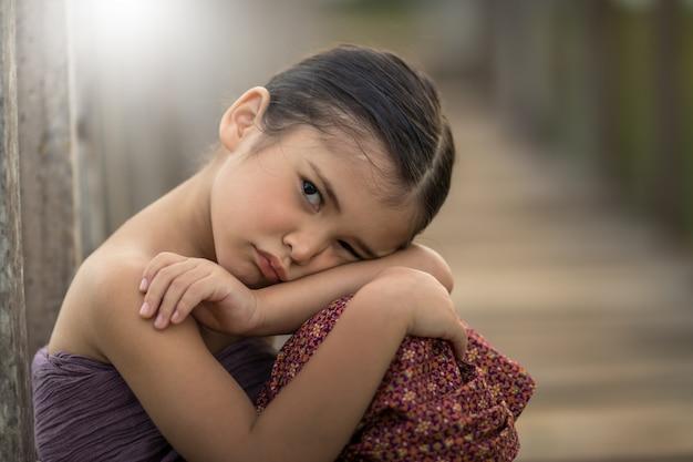 Mała tajska dziewczyna w tajskim stroju myśli o czymś samotnym.