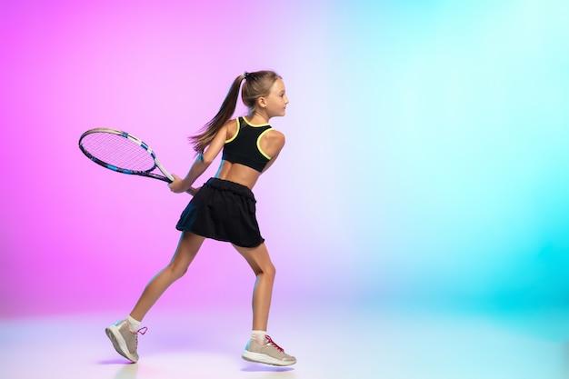 Mała tenisistka w czarnej odzieży sportowej odizolowana na gradientowej ścianie w świetle neonowym