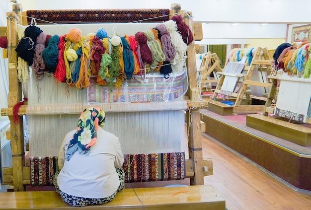 Mała tkalnia. kobieta za pracą - tkanie dywanu z jedwabiu (ręcznie wykonane)