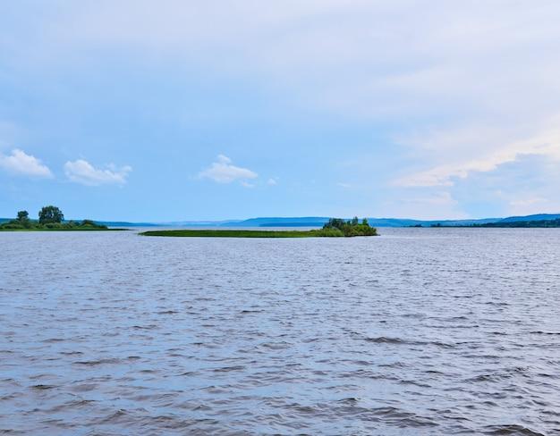 Mała trzcinowa wyspa pośrodku szerokiej rzeki