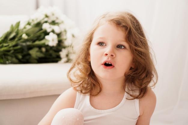 Mała trzyletnia dziewczynka o zdziwionej twarzy. słodkie dziecko w domu. jasne wnętrze i białe kwiaty na tle
