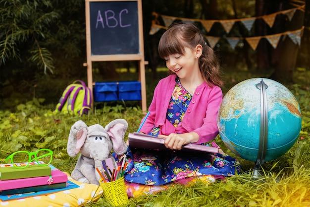 Mała uczennica czyta książkę. powrót do szkoły. edukacja, szkoła, dzieciństwo