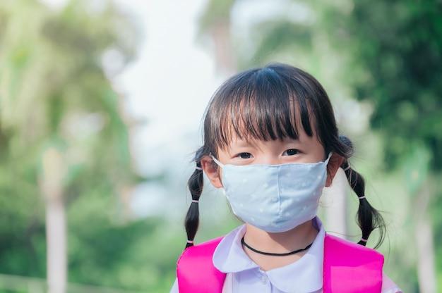 Mała uczennica ma maskę chroniącą się przed koronawirusem covid-19, gdy dziecko idzie do szkoły