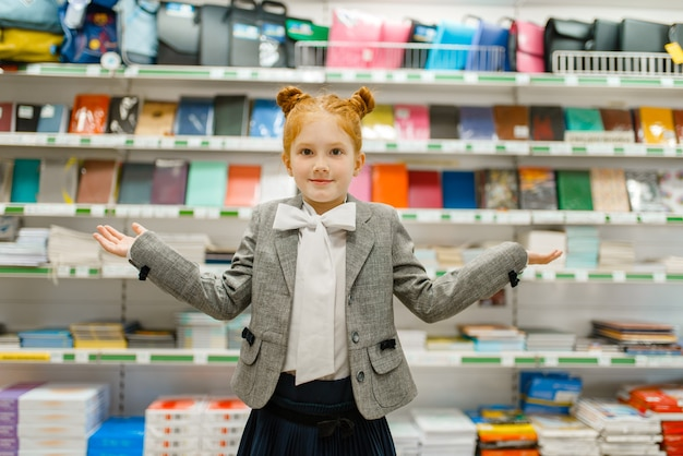 Mała uczennica na półce w sklepie papierniczym, widok z przodu