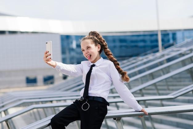 Mała uczennica o rozmowie telefonicznej z przyjacielem. nowoczesna komunikacja życia. życie w erze cyfrowej.