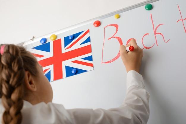 Mała uczennica pisząca napis z powrotem do szkoły na tablicy