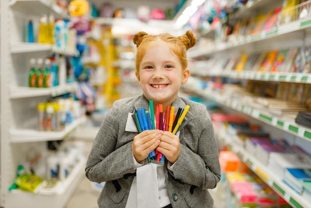 Mała uczennica trzyma kolorowe markery, robi zakupy w sklepie papierniczym