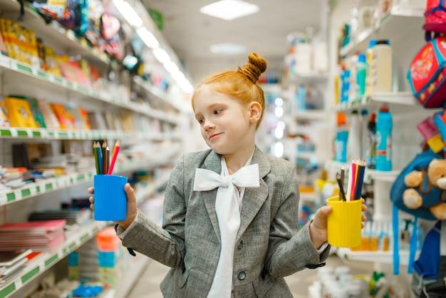Mała uczennica trzyma okulary z ołówkami, robi zakupy w sklepie papierniczym