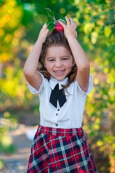 Mała uczennica trzyma w głowie czerwone jabłko, uśmiecha się do kamery. dzieciństwo. edukacja. pojęcie reklamy i ludzi.