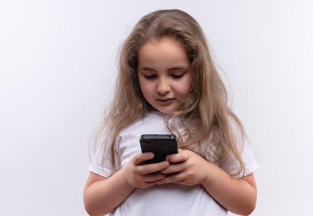 Mała uczennica ubrana w białą koszulkę gra z telefonem na odosobnionej białej ścianie