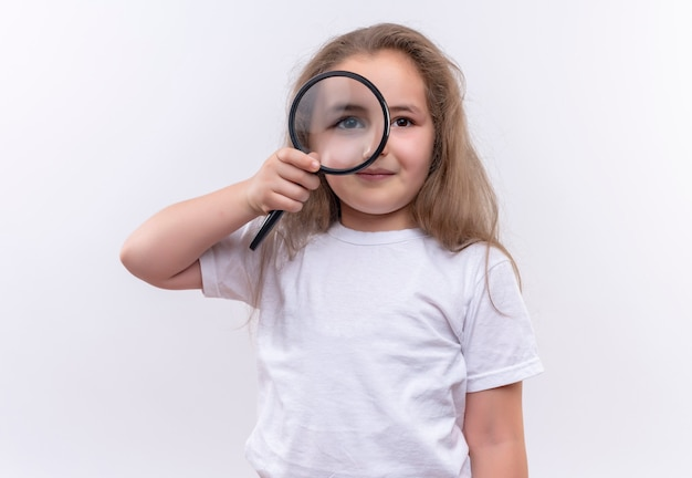 Mała uczennica ubrana w białą koszulkę patrząc przez lupę na odizolowanej białej ścianie