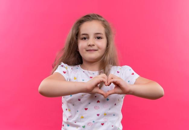 Mała uczennica ubrana w białą koszulkę z gestem serca na na białym tle różowej ścianie