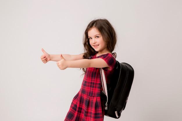Mała uczennica uśmiecha się i kciuki do góry
