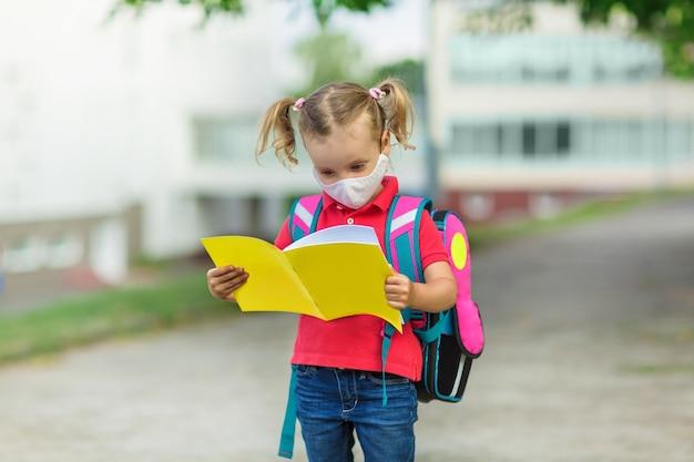 Mała uczennica w masce medycznej wychodzi ze szkoły z żółtym notesem w dłoniach