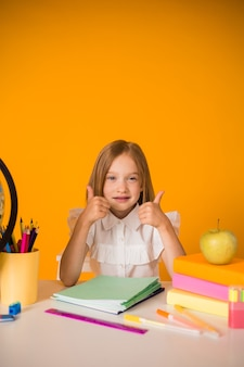 Mała uczennica w mundurku siedzi przy stole z przyborami szkolnymi na żółtym tle z miejscem na tekst
