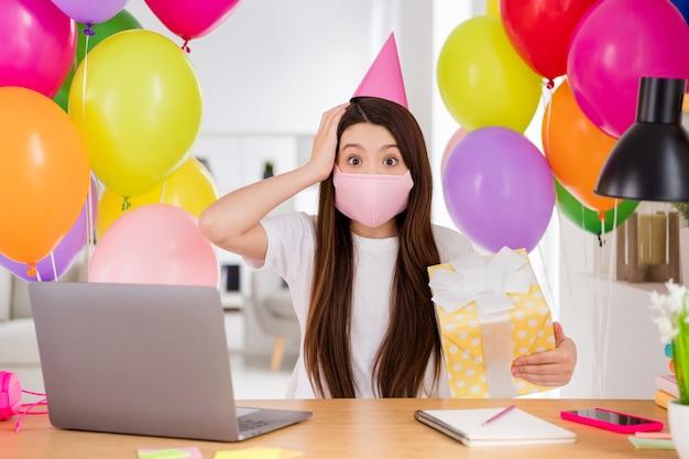 Mała uczennica w różowej masce medycznej świętuje przyjęcie urodzinowe w pomieszczeniu