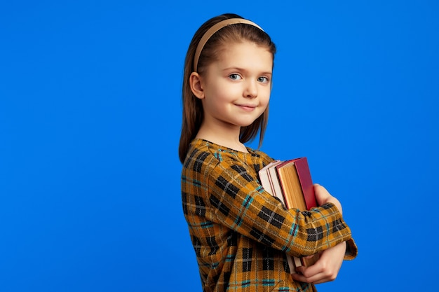 Mała uczennica w zwykłej sukience trzymająca książki przed niebieską ścianą