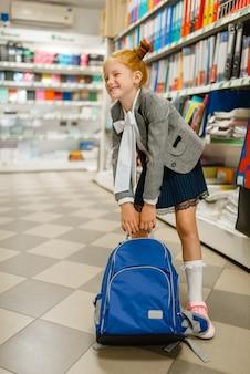 Mała uczennica z ciężkim szkolnym plecakiem na półce w sklepie papierniczym