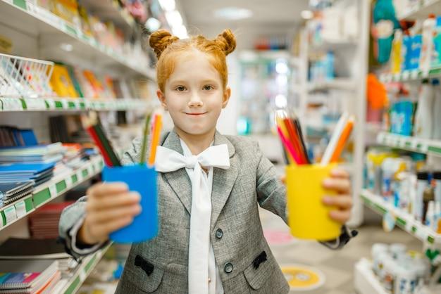 Mała uczennica z kolorowymi ołówkami, zakupy w sklepie papierniczym