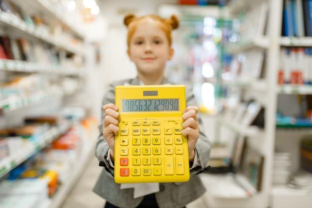 Mała uczennica z żółtym kalkulatorem, zakupy w sklepie papierniczym