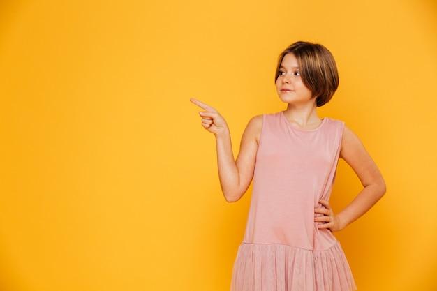 Mała ufna dziewczyna wskazuje przy kopii przestrzenią odizolowywającą