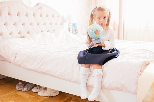 Mała urocza blondynka w mundurku szkolnym i białych polach golfowych siedzących na ławce w jej sypialni i szokuje pierwszego dnia w szkole.
